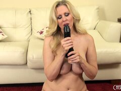Julia Ann likes fucking her pie hole with a big black dildo on the floor