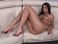 Sexy brunette Zafira enjoys fingering her pussy on a sofa