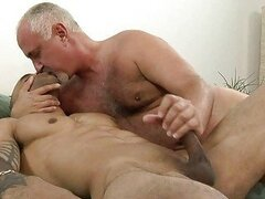 Sexy tattooed gay giving handjob to his older daddy