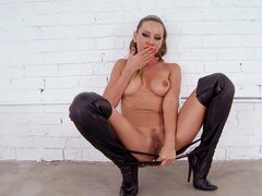 Oiled pornstar wearing boots bangs her pussy with her fist