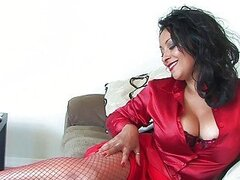 Sexy brunette in red outfit and stockings plays wit her big tits