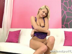 Attractive blonde with lovely tits sits on the couch enjoying her time with sex toys