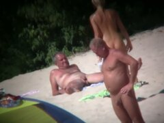 Voyeur on the beach capturing a tanned...
