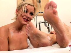 Lesbian couple shares a sensual bath and lick each other's feet