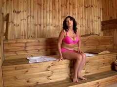 Big breasted woman oils up in sauna