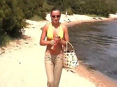 A hot girl takes her bikini off and shows her body at the beach