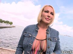 After this busty blonde MILF's walk on the beach, she bares her juggs