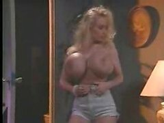 A slutty blonde chick with immense headlamps has them kissed and caressed