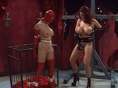 Submissive Female Kisses Busty Dominatrix's Feet Wearing a Latex Bondage Hood