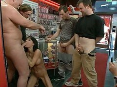 Several Cocks and Toys Fucking a Brunette Beauty In Sex Shop Gangbang
