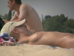 Two pretty, naked girls sunbathing at the sandy beach