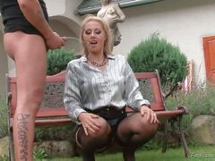A blonde, fully dressed girl is sitting on her hunches in the garden. A guy stands next to her, pissing all over her. She spreads her legs and pulls her panties aside, showing her pussy off. A little later she pisses over the guys dick.