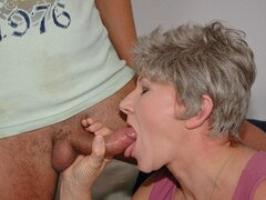 A grey haired granny gets down on her well marked knees to suck a hunk's hammer