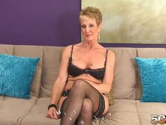 An older MILF that is in need of a good fucking sits on the sofa and strips