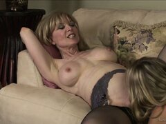Beautiful blonde cougar gets her younger girlfriend to eat her out