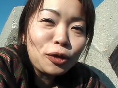 Mature Tomomi Kobayashi takes a piss after masturbating on a beach