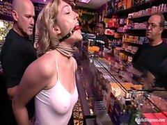 A bold blonde babe is bound, gagged and forced to fuck in a random store