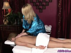 Sexy blonde babe in a slinky robe gives her gal pal a lesbian massage