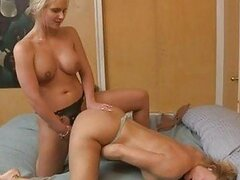 Two blonde mature lesbians play with strapon in bedroom